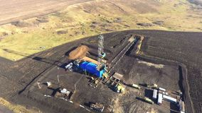Drilling derrick. Aerial filming. Drilling derrick and trucks nearby. Natural gas field. Drone filming. The drone turns around a tower. Ukraine, Kharkiv region stock video footage