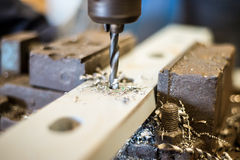 Drilling in flat steel plate with bench drill. Stock Photos