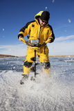 Drilling a Hole. Ice flies everywhere as an ice fisherman uses an auger to make his fishing hole Stock Images