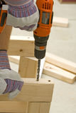 Drilling hole. Man drilling a hole into wood with cordless drill Royalty Free Stock Photo