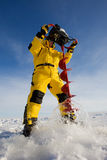 Drilling a hole. Ice fisherman drilling a hole with a power auger Royalty Free Stock Photography