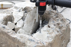 Drilling hole into concrete. Breaking concrete with drill Royalty Free Stock Image