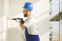Drilling the hole with a drill in the wall. Royalty Free Stock Images