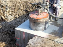 Drilling hole. Drilling huge hole on concrete plate Stock Image