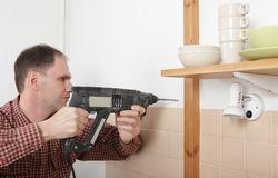 Drilling the hole in a kitchen wall Royalty Free Stock Images