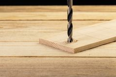 Drilling hole in to wooden plank. Carpentry concept stock photography