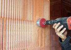 Drilling a hole in the wall, a man at work Royalty Free Stock Photos