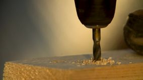 Drilling holes in a wooden bar with a drill and a hand drill with a high frame rate. Drilling hole on a wood panel with a high speed camera, phantom flex stock footage