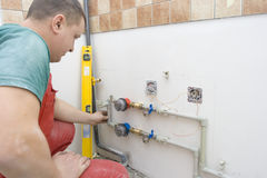 Drilling holes for the fixing water pipes stock photos