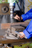 Drilling machine. Machinist working on industrial drilling machine in workshop Stock Photography