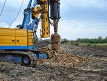 Drilling machine on construction site. The yellow drilling machinery on construction site Stock Photos