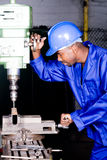 Drilling machine operator. African american machinist operator operating a drilling machine Royalty Free Stock Images