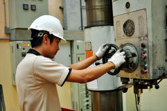 Drilling machine operator. Thai machinist operator operating a drilling  machine Royalty Free Stock Images