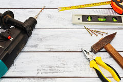 Construction tools on wooden surface with copyspace. Drilling machine and some hand tools lie on rough wooden work desk. Handyman tools prepared for work. Place royalty free stock images