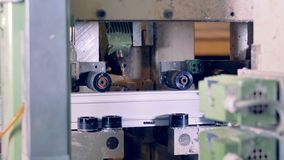 Horizontal rollers move a PVC profile inside a drilling machine. stock footage