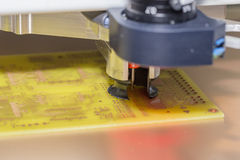 Drilling PCB holes. CNC drill machine drilling a printed circuit board. Drilling PCB holes. Selective focus and shallow dof Stock Photography
