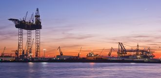 Drilling platform in dock. Big drilling platform in repair in the harbour at sunset Stock Image