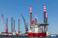 Drilling platform in the port of Amsterdam. Maintenance on a red and white drilling platform with cranes in the port of Amsterdam royalty free stock photos