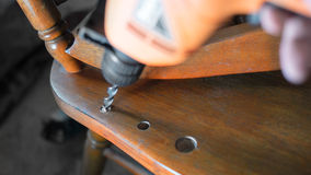 Drilling. Repairing of old chair. Selective focus on drill, shallow dof. Royalty Free Stock Images