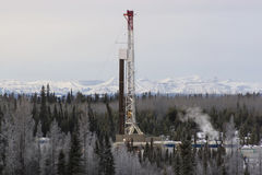 Drilling Rig in the Mountains. A tall oil drilling rig in the Alberta mountains Royalty Free Stock Image