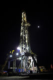 Drilling Rig at Night. With shining lights and the moon shinning Stock Images