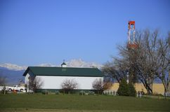 Drilling Rig Oil well green barn with mountains stock images
