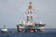 Drilling rig and supply vessel. Stationary dynamic positioned drilling rig in offshore area with a supply vesel along side.  Coast of Brazil Stock Photo