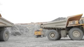 Drilling rig and two heavy dump trucks. Open pit stock video footage