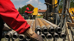 Drilling Rig and Two Oil Workers. Oil drilling rig workers lifting drill pipe