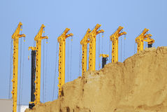 Drilling rigs. Construction site with drilling rigs behind a sand hill Royalty Free Stock Photos