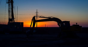 Drilling rigs. Drilling rigs and excavator at sunset in the steppe Royalty Free Stock Photos