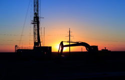 Drilling rigs. Drilling rigs and excavator at sunset in the steppe Royalty Free Stock Images