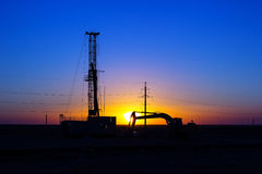 Drilling rigs. Drilling rigs and excavator at sunset in the steppe Royalty Free Stock Image