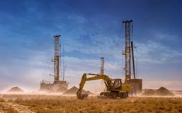 Drilling rigs. And excavator work in the desert. Strong wind, a lot of dust Stock Photos