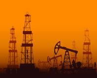 Drilling rigs and oil pumps at sunset Royalty Free Stock Photo