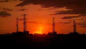 Drilling rigs. Operate in the steppe at sunset Stock Photos