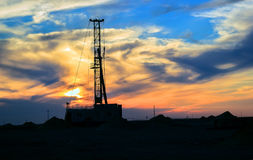 Drilling rigs. Drilling rigs operate in the steppe at sunset Stock Photos