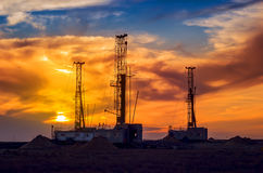 Drilling rigs. Drilling rigs operate in the steppe at sunset Royalty Free Stock Photo