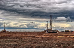 Drilling rigs.. Drilling rigs operate in the steppe under the clouds Royalty Free Stock Image