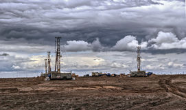 Drilling rigs. Drilling rigs operate in the steppe under the clouds Stock Images