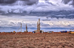 Drilling rigs. Drilling rigs operate in the steppe under the clouds Royalty Free Stock Image