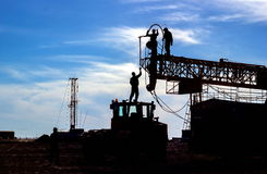 Drilling rigs. Silhouettes of drilling rigs and workers against the sky Stock Images