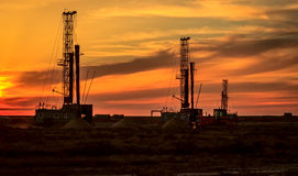 Drilling rigs at sunset. Drilling rigs operate in the steppe at sunset Royalty Free Stock Photo