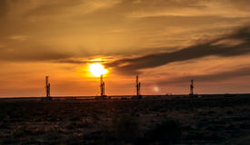 Drilling rigs at sunset. Drilling rigs operate in the steppe at sunset Stock Image