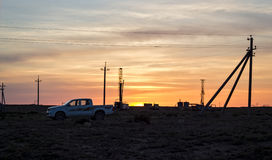 Drilling rigs at sunset. Drilling rigs operate in the steppe at sunset Stock Images