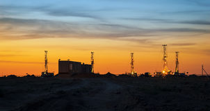 Drilling rigs at sunset. Drilling rigs operate in the steppe at sunset Royalty Free Stock Photos