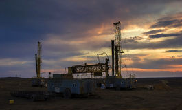 Drilling rigs sunset. Drilling rigs at sunset in the steppes of southern Kazakhstan. Betpakdala Stock Photos
