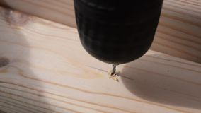 Drilling a small hole in a pine wood plank with a drill bit. Closeup of drilling a small hole in a thin pine wood plank with a drill bit stock video