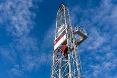Drilling tower. High drilling towers standing in between the blue sky and white clouds Royalty Free Stock Images