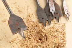Drilling with a vane drill in chipboard. Carpentry work in a carpentry workshop. Light background royalty free stock photo